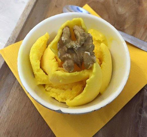 una coppa di gelato con sopra una noce