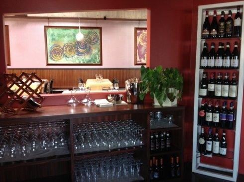 dei bicchieri in un mobile basso e i vini negli scaffali