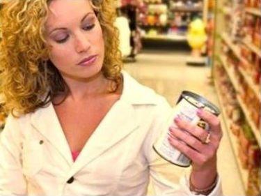 una donna con in mano un barattolo al supermercato