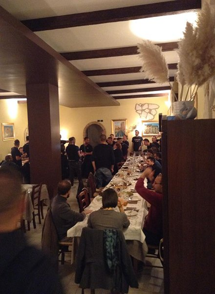 Delle persone mentre mangiano ad un tavolo lungo e un gruppo di persone mentre suonano