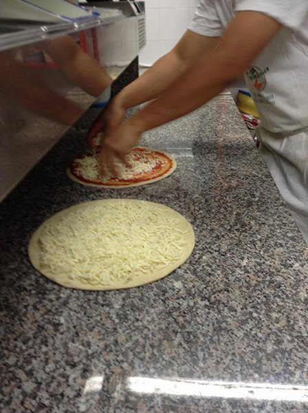 Un pizzaiolo mentre farcisce una pizza con formaggio