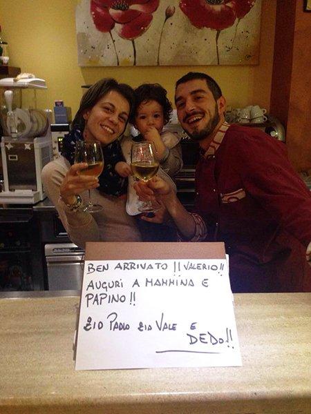 Una donna con un bambino in braccio e un uomo in posa con un calice di vino all'interno di un ristorante
