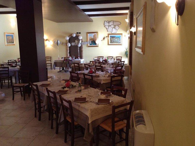 interno di un ristorante con dei tavoli apparecchiati con piatti, bicchieri, fiori in mezzo e  in fondo un altro  tavolo con un bouquet di fiori e decorazioni con palloncini a forma di cuore