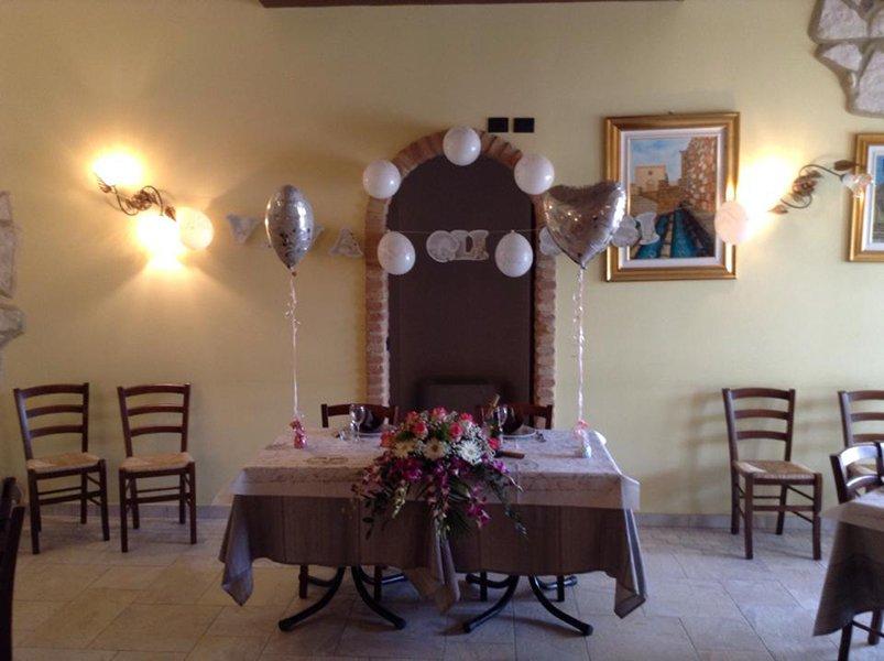 Un tavolo apparecchiato e decorato con fiori e palloncini