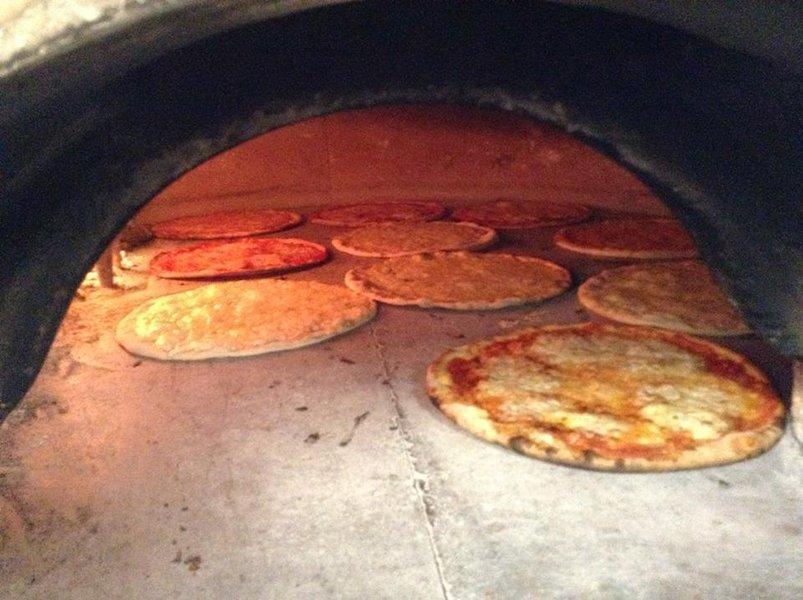 Delle pizze all'interno di un forno a legna
