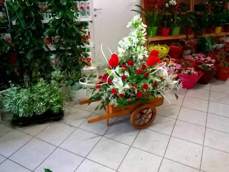 Un vaso a forma di un carrello di legno con delle rose