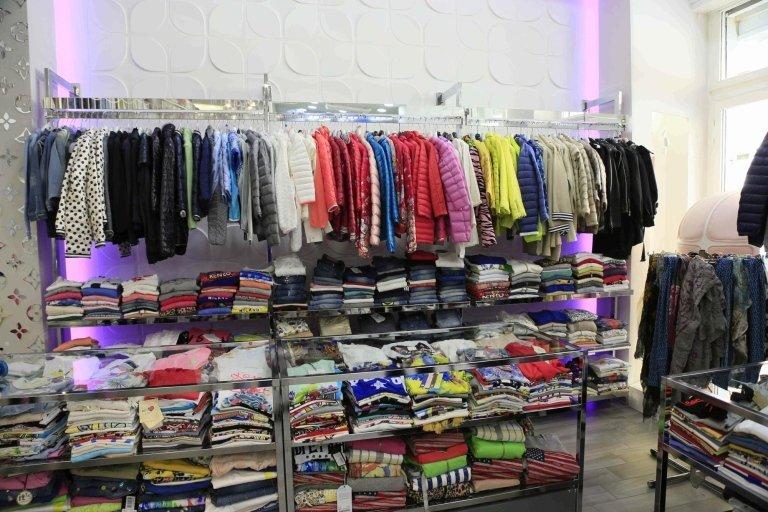 vestiti su appendiabiti e nel scaffalatura in negozio di abbigliamento