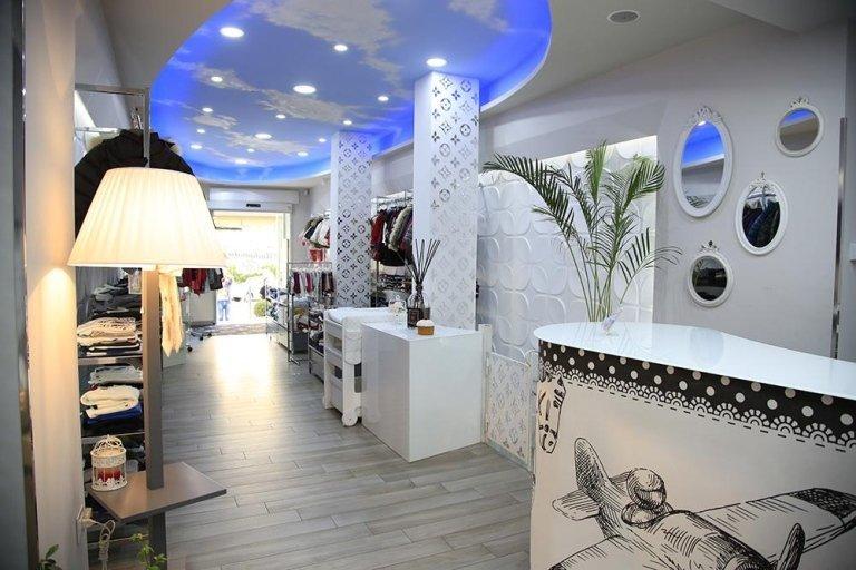 vista interna di negozio MADAMALÙ con centralino, lampadina, parete bianca e scaffalatura in negozio vestiti