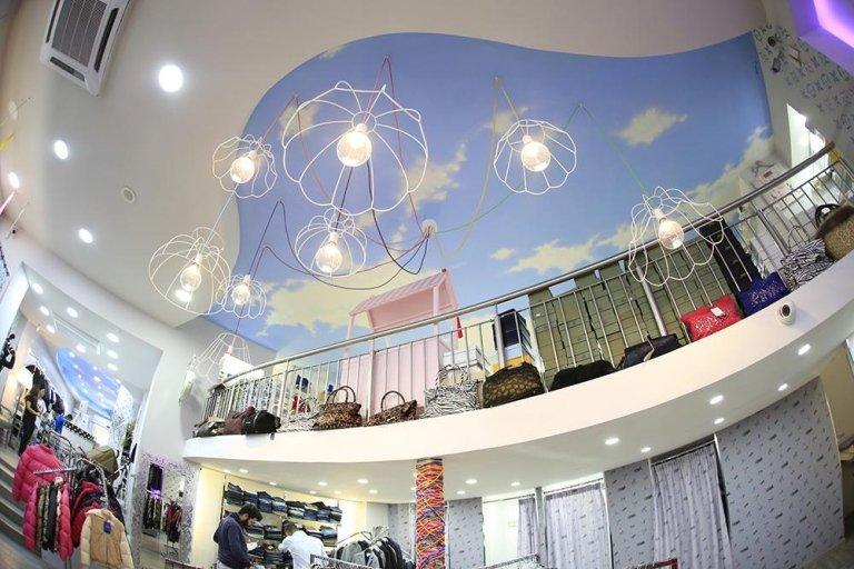 negozio di abbigliamento con soffitto decorato e borse in scaffalatura