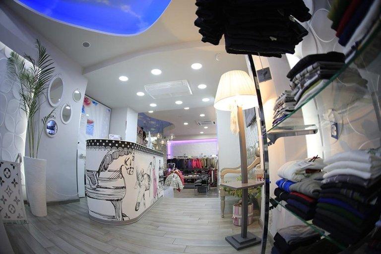 vista frontale  di negozio bancone  con vestiti su appendiabiti , nel scaffalatura, vaso, lampadina e lucido in soffitto