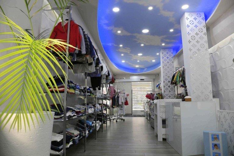 vista laterale di negozio con vestiti su appendiabiti e nel scaffalatura