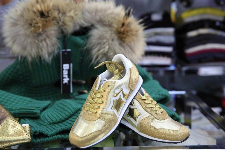 scarpe oro e bianco con abbigliamento su un bancone di negozio per mostra