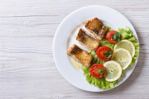 Piatto di pesce con limone e pomodoro