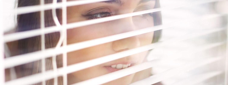 Waikato lady looks through blinds