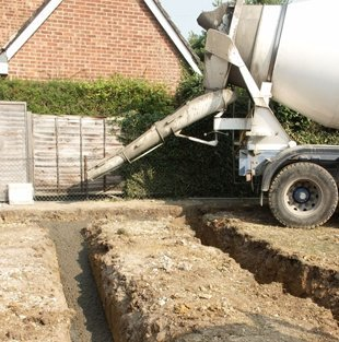 Grey cement mixer pouring cement into driveway