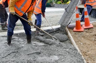 Grey cement being poured into road