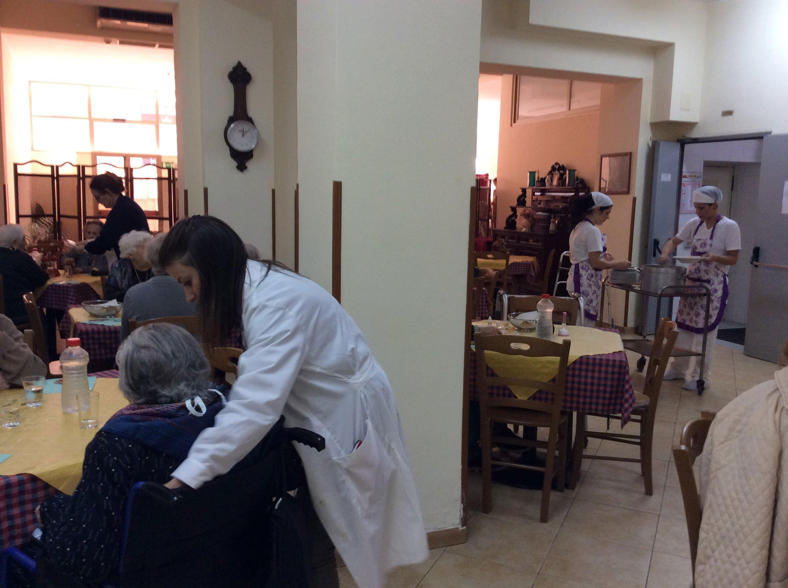 un' infermiera sta aiutando una donna sulla carrozzina a rotelle seduta al tavolo in una mensa di una casa di cura e in fondo si vedono degli addetti con un carrello che stanno riempiendo i piatti