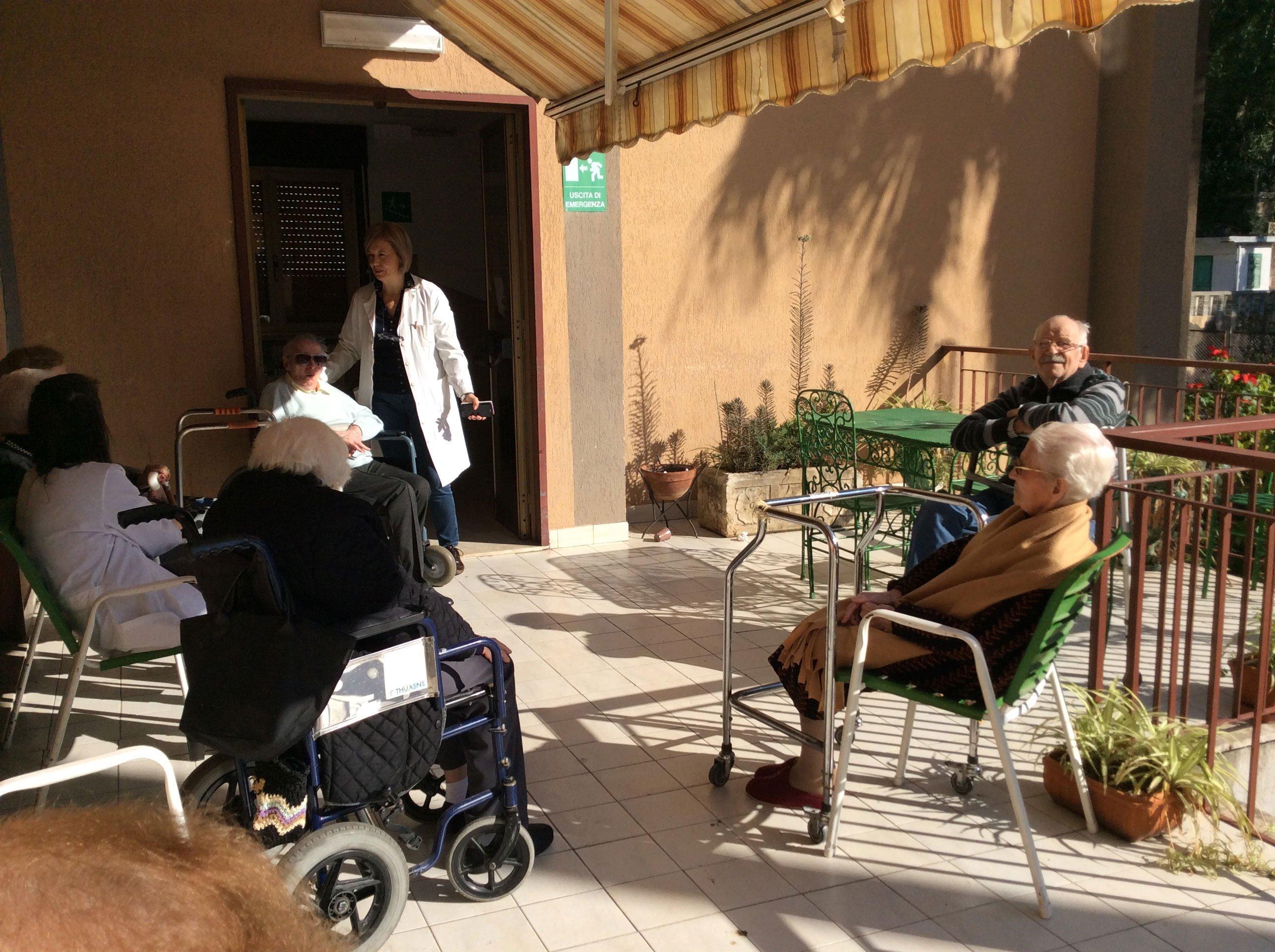 delle persone in carrozzina a rotelle e alcune sedute in un terrazzo vicino a loro,in piedi, c'e' una donna con il camice bianco