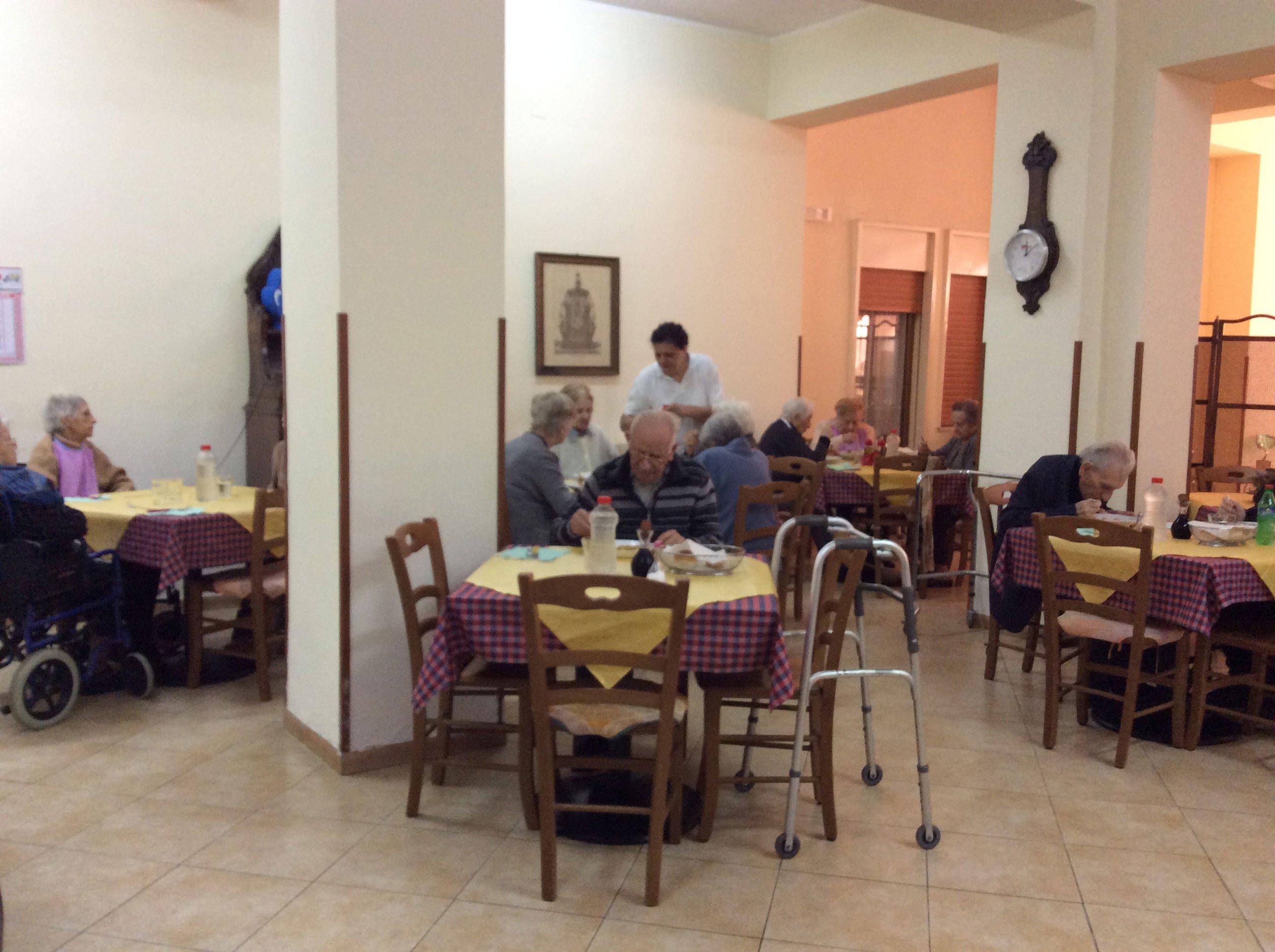 interno di una mensa in una casa di riposo con un uomo al tavolo che sta mangiando e accanto c'e' un deambulatore
