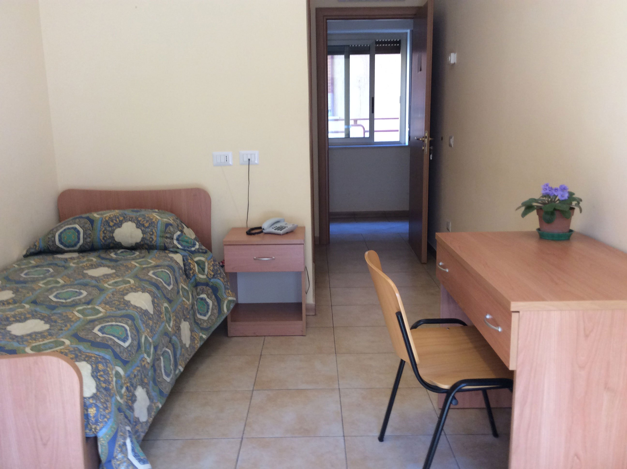 una camera da letto di una casa di riposo con sulla sinistra un letto e un comodino in legno e sulla destra una scrivania con sopra un vaso di fiori e una sedia