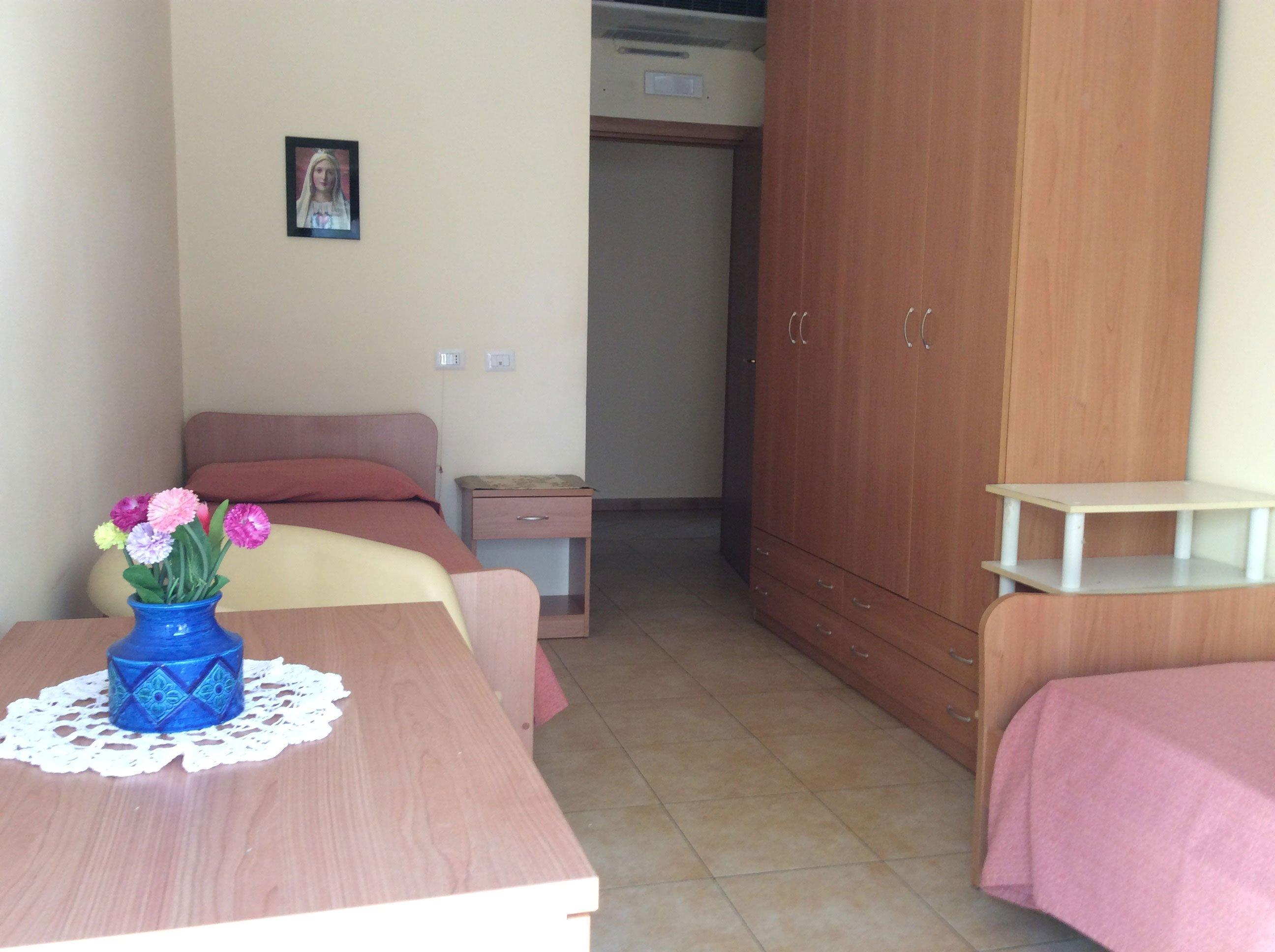 una camera da letto con sulla sinistra un letto, sulla destra un armadio, una scrivania con sopra un vaso di fiori e si intravede un altro letto