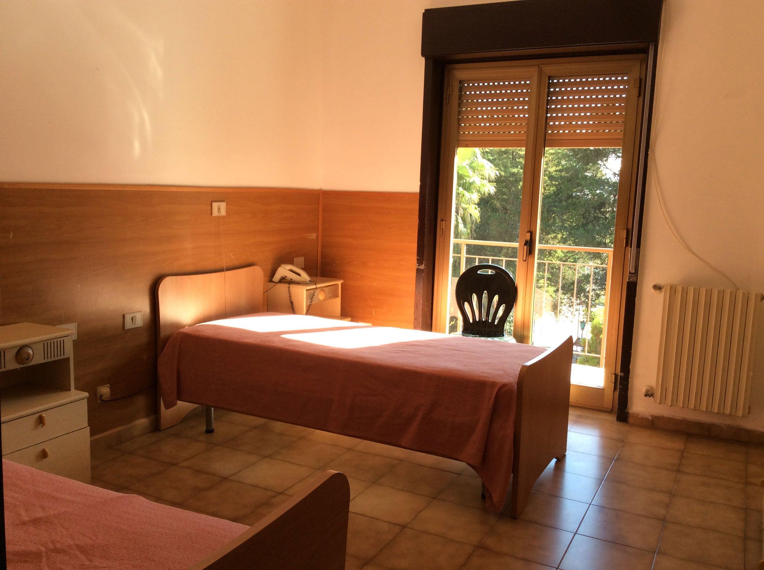 una stanza con due letti, un comodino, una sedia davanti alla finestra e la tapparella abbassata a meta'