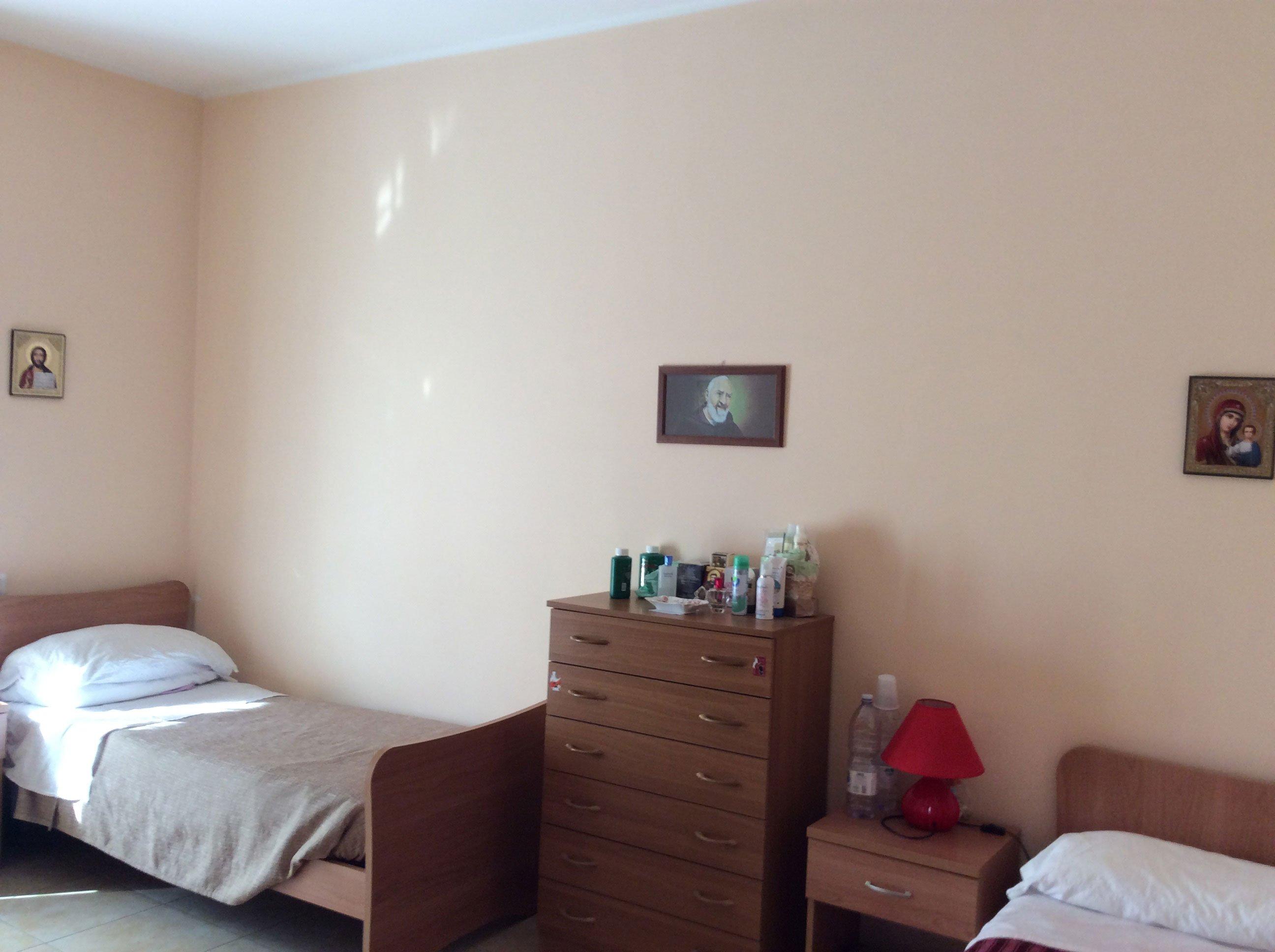 camera da letto con sulla sinistra un letto, in mezzo una cassettiera di legno e sulla destra un comodino con una lampada rossa con un letto accanto