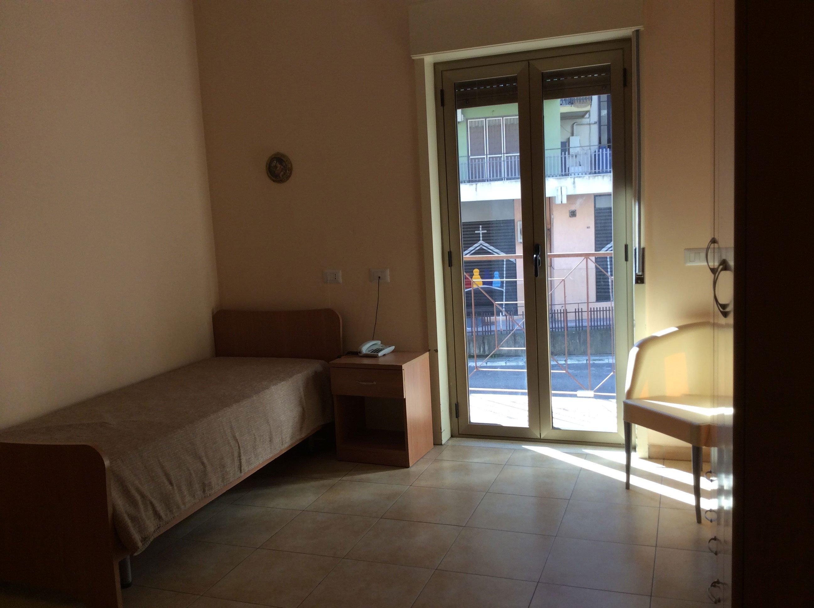 stanza con un letto e un comodino sulla sinistra, in mezzo una porta finestra e sulla destra una sedia