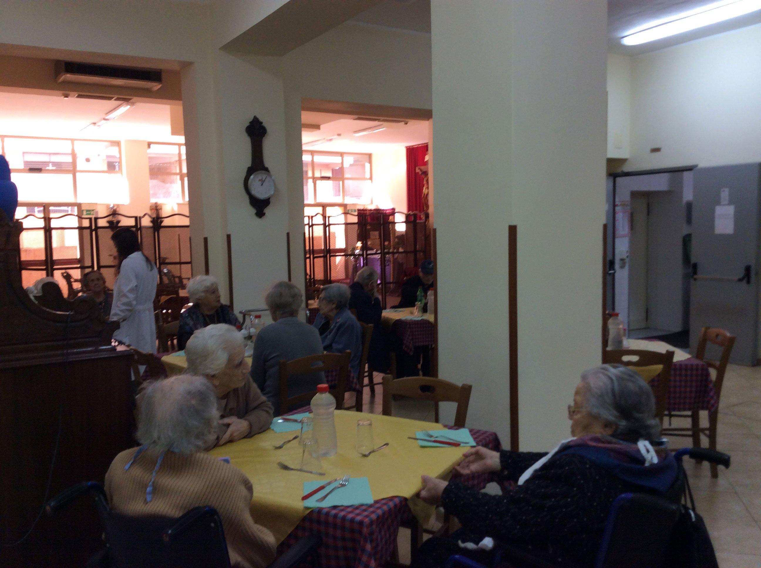 delle persone sedute ai tavoli all'interno della mensa della casa di riposo