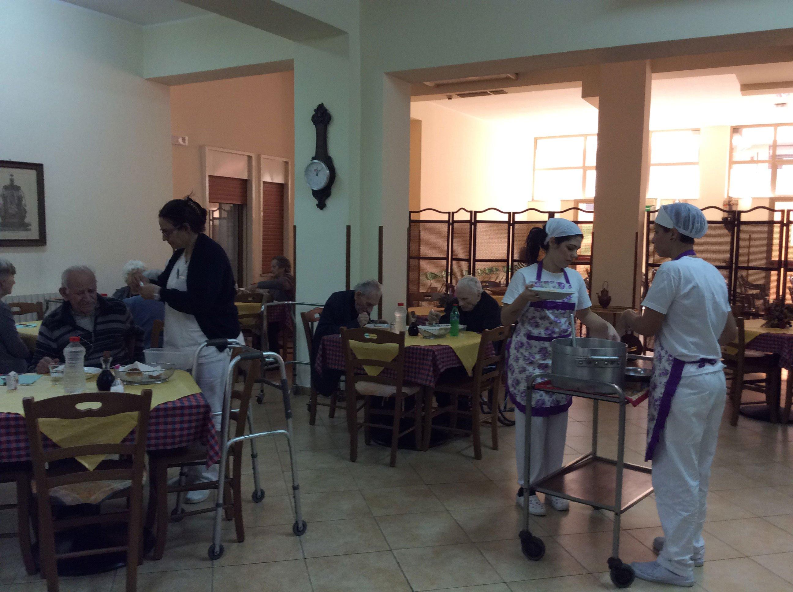 Persone seduti all'interno della mensa della casa di riposo e due camerieri con grembiule di color bianco e viola al carrello con pentole