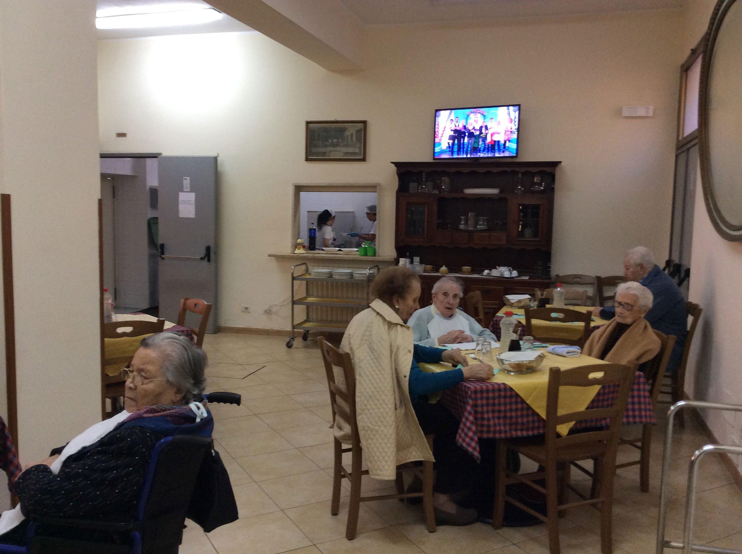 mensa all'interno della casa di riposo con persone sedute ai tavoli e in fondo un mobile in legno con sopra una tv