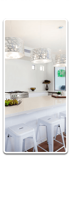 white kitchen worktop with chairs underneath and lighting above