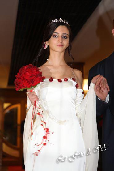 una sposa con un abito di color bianco con disegni di rose di color rosso