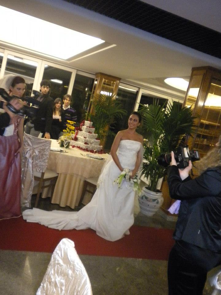 una sposa in posa e intorno delle persone che scattono le foto