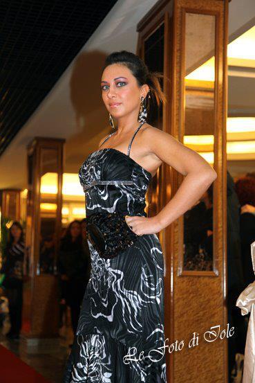 una donna in posa con un abito di color nero e argento
