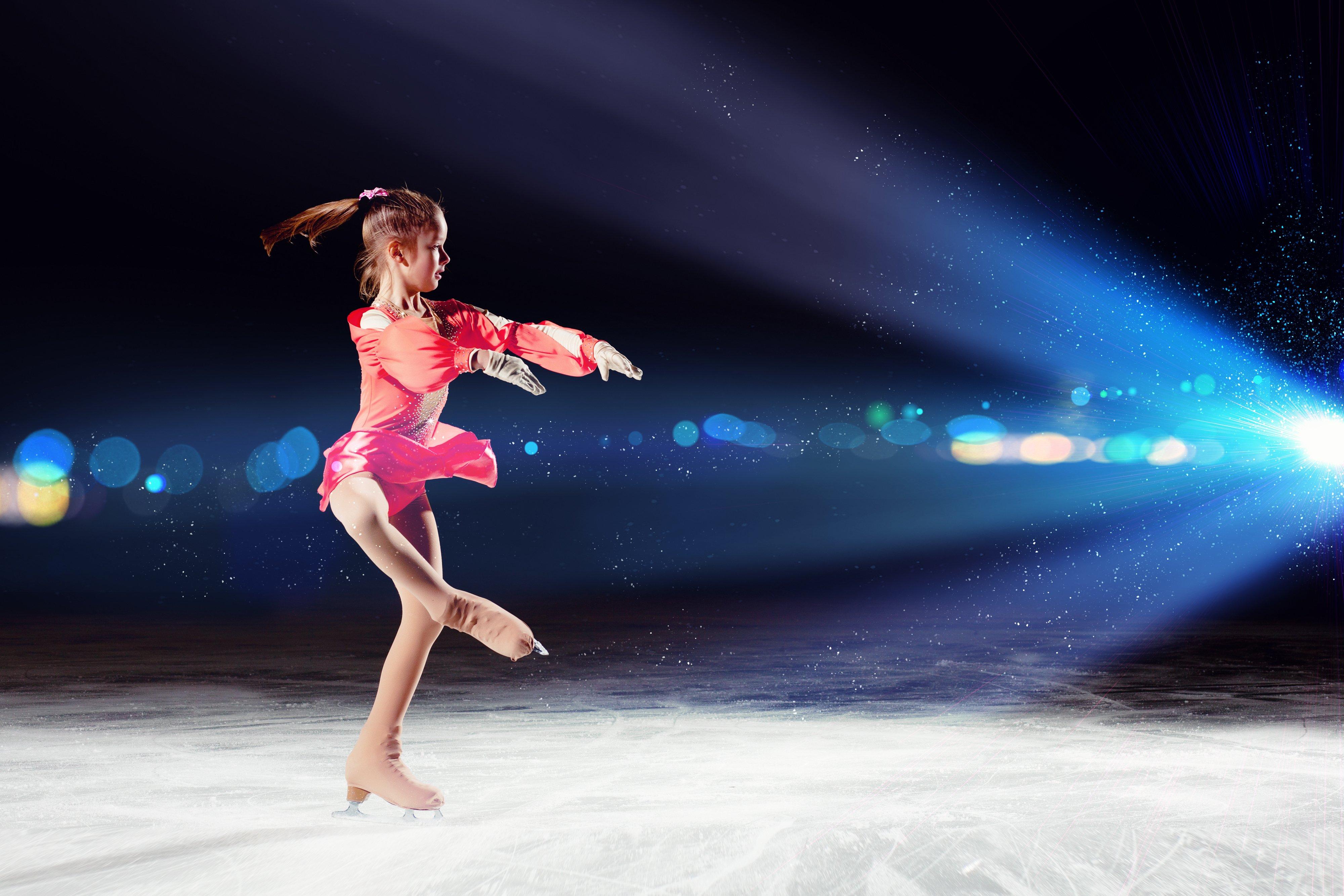 una bambina con un abito rosso durante un'esibizione  di pattinaggio artistico