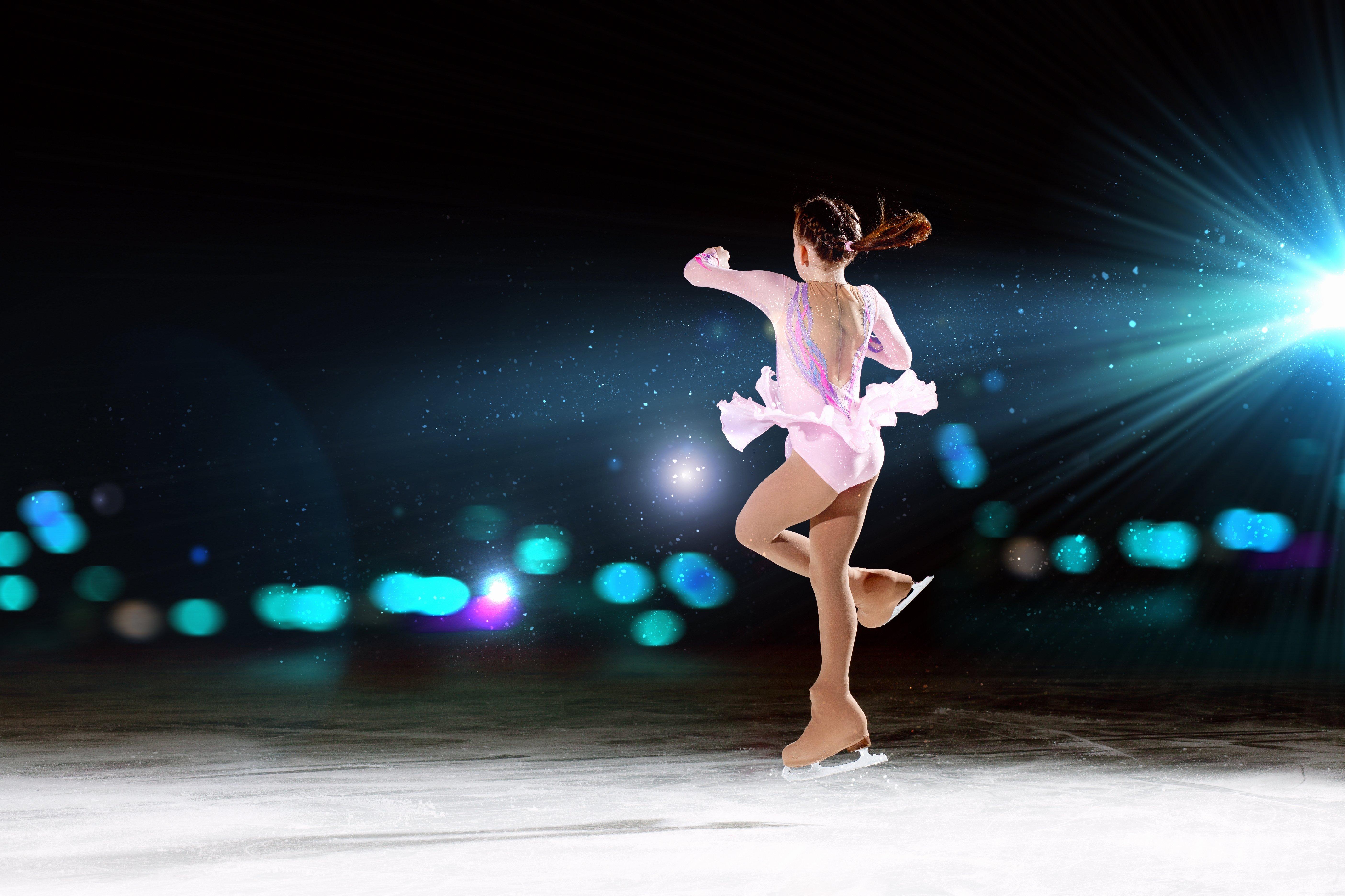 una bambina girata che pattina sul ghiaccio