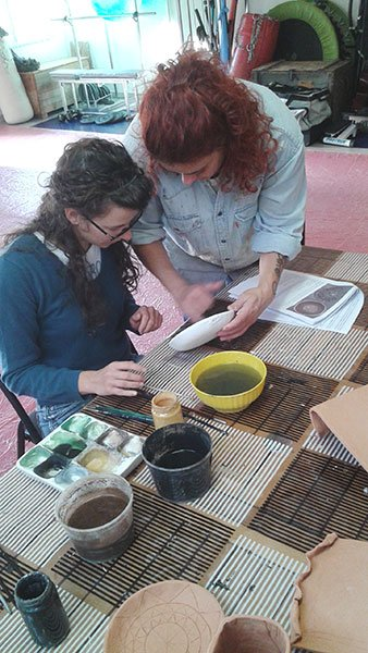 insegnate che mostra ad un allievo le tecniche di pittura su ceramica