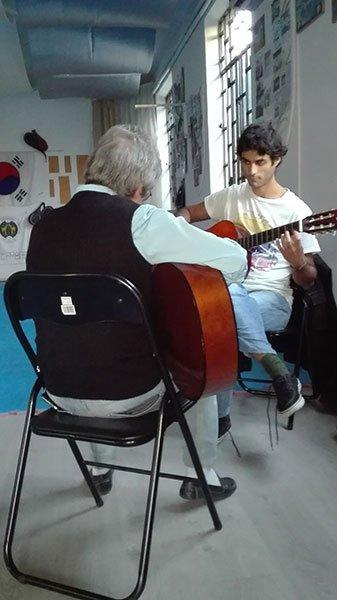 Maestro di chitarra che insegna a giovane allievo come suonare