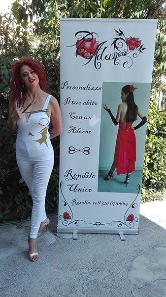 Donna vestita di bianco accanto a manifesto pubblicitario di Mostra di abiti da cerimonia