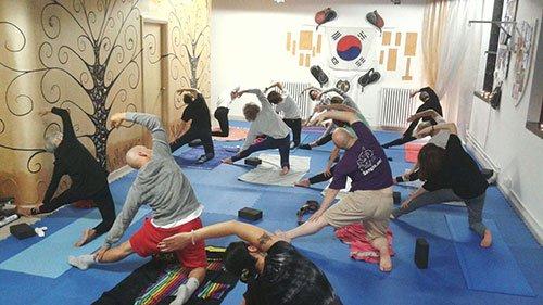 gruppo di persone intente a fare lezione di hatha yoga