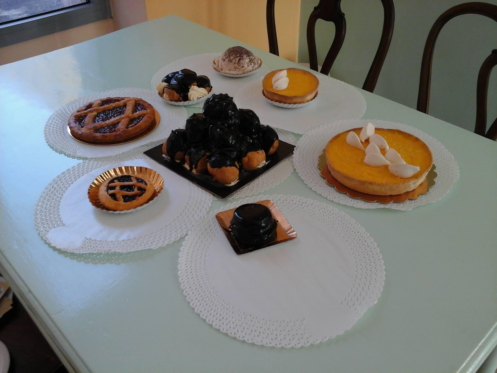 Tavola con crostata al limone, marmellata, Zuccotto, profiterol al cioccolato e panna
