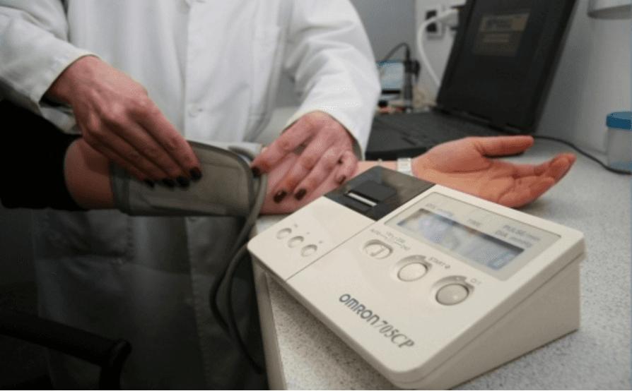 dottoressa che misura la pressione sanguigna di una paziente con misuratore elettronico