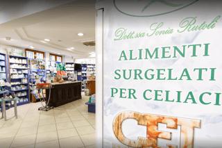 primo piano cartello alimenti surgelati per celiaci con farmacia sullo sfondo