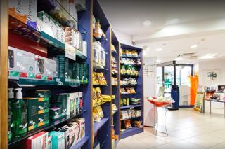 scaffale con prodotti farmaceutici ed ingresso farmacia sullo sfondo