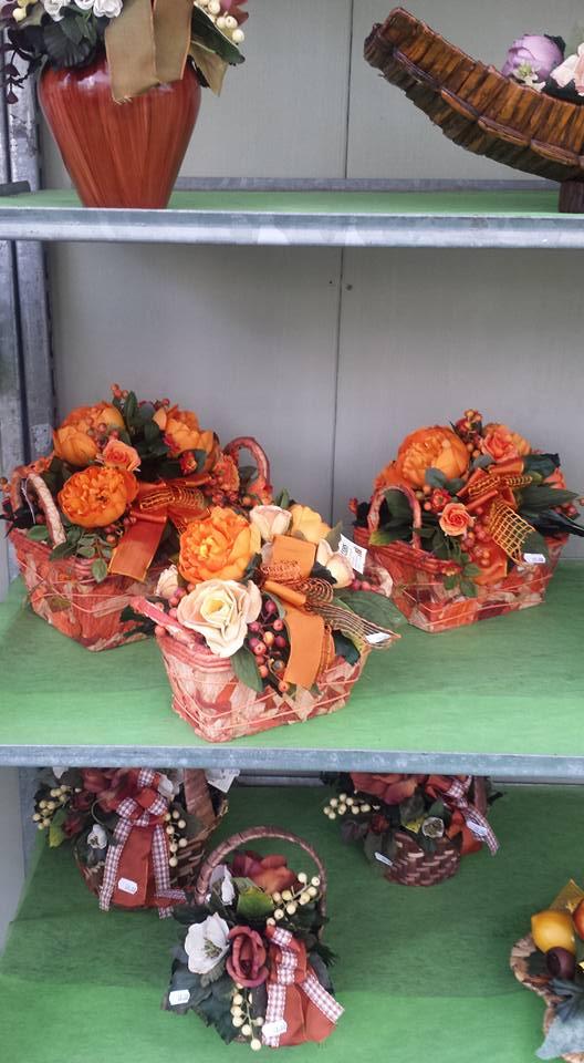 2 mensole, una con 3 cestini con dei fiori bianchi e bordeaux e l'altra con 3 cestini con fiori arancioni