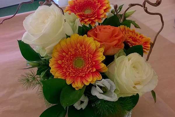 Un vaso di vetro quadrato con fiori di color arancione e rose bianche appoggiato su un tavolo di legno