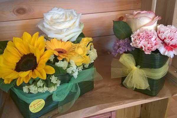 Cassetta di legno con due vasi di fiori, una e' composta da girasoli e l'altra da rose