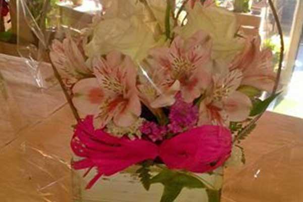 Un vaso di legno dipinto in bianco, con orchidee e decorazioni a forma di cuore