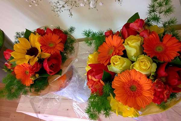 Due bouquet di girasole, fiori arancioni e rose gialle appoggiati su una mensola